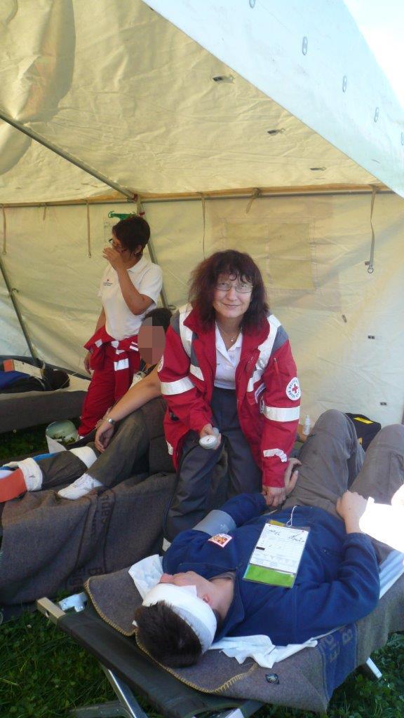 Helferin Theresia beim Blutdruck messen eines Verletzen